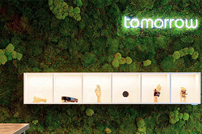 "Green moss wall with a bright neon font ""tomorrow"" on it"
