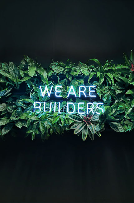 "neon lettering with the words ""We are Builders"" on a plant wall"