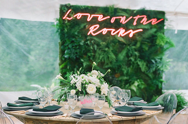 "Plant wall with pink neon lettering with the words ""Love on the Rocks"""