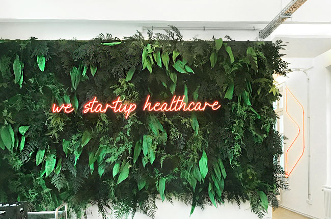 """We are healthcare"" Lettering made of red LED neon attached to a plant wall"
