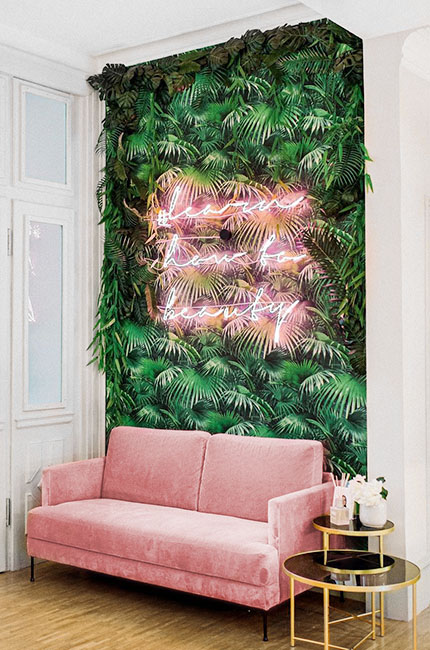 neon lettering on a plant wall