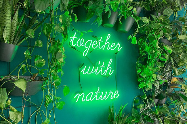 "A neon sign with the words ""Together with nature"" on a plant wall"