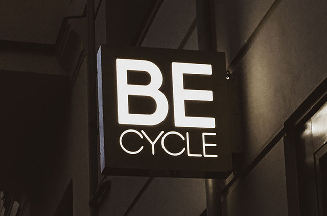 Becycle Berlin logo as a nose sign glowing at night mounted on an exterior facade