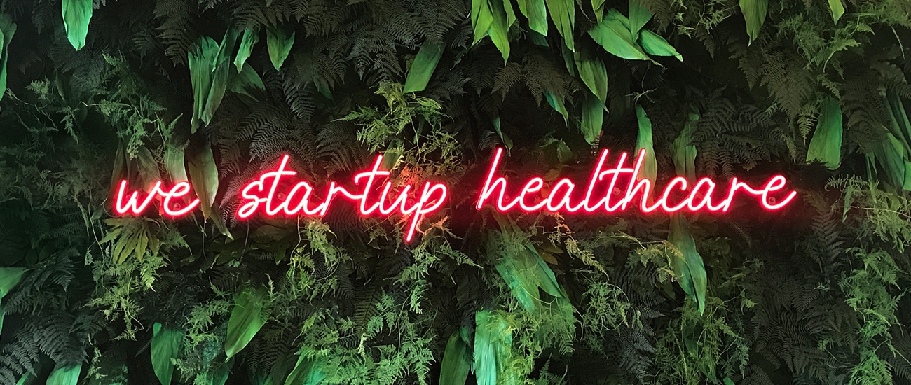 We are healthcare Schriftzug aus rotem LED Neon an einer Pflanzenwand befestigt