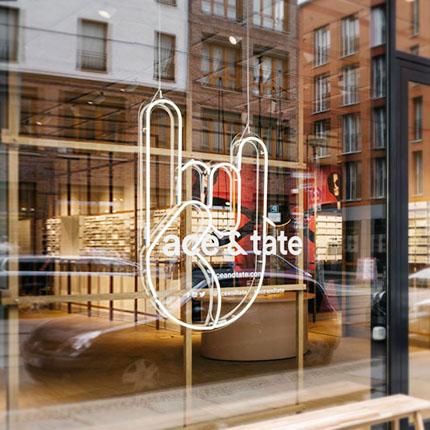 Ace and tate Ladenfront mit einem Neonzeichen im Schaufenster