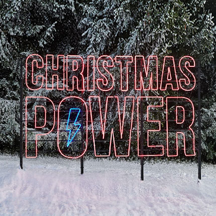 Large neon lettering with the words Christmas Power in a natural landscape
