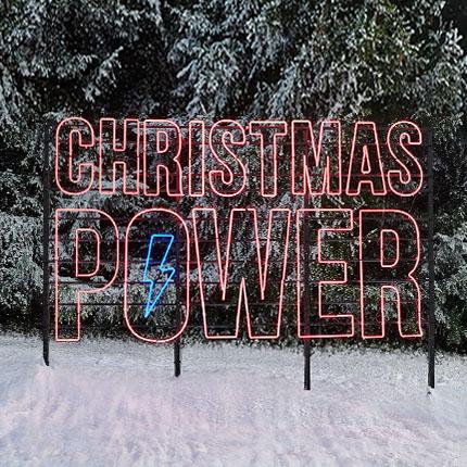 Großer Neonschriftzug mit den Worten Christmas Power in einer Naturlandschaft