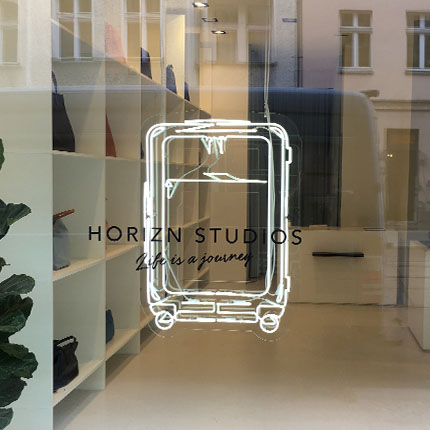 Horizn Studios suitcase made of bright neon light in a shop window hanging from the ceiling