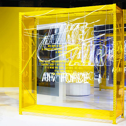 Nike showroom in which there is a yellow XXL frame in which the Nike logo made of neon light was fixed