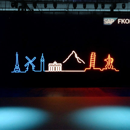 A trade show booth from the SAP brand with various landmarks in neon attached to a wall