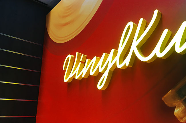 "Dussmann yellow LED neon sign with the words "" Vinyl"""