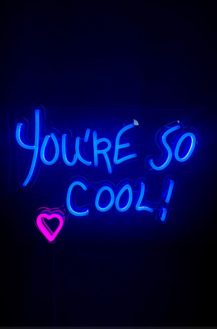 "LED neon lettering with the words ""You're so cool"" mounted on a plexiglass panel"