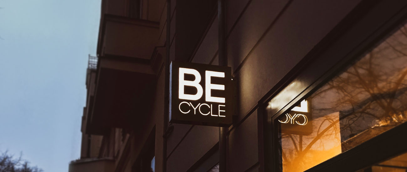 Becycle Berlin logo mounted as a nose-shield glowing at night on an exterior facade