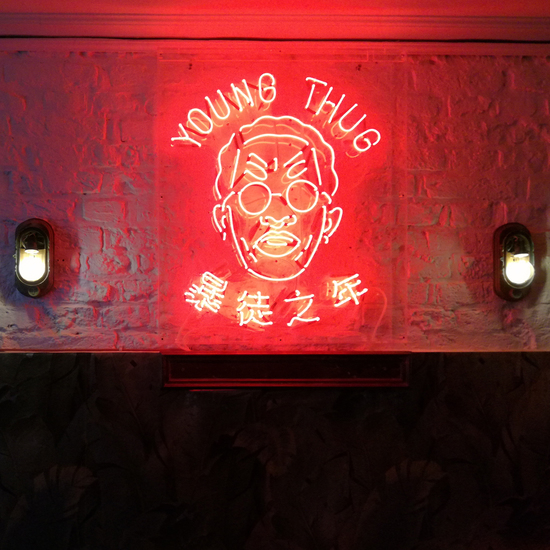 Red Young Thug logo in neon letters on a wall