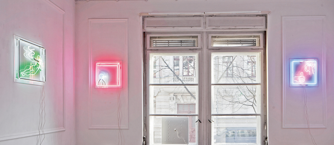 A white room with small pictures made of neon on the wall