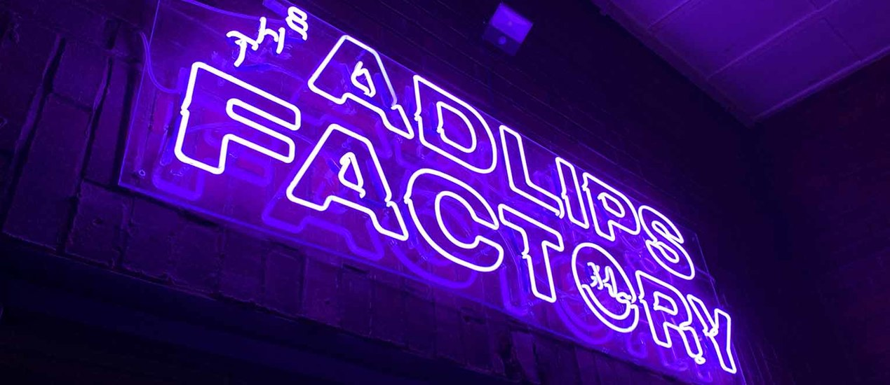 Adlips Factory logo installed in purple neon light on an outdoor patio