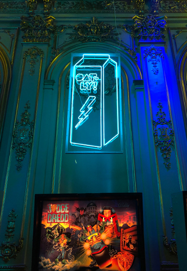 Oatly milk carton made of blue neon light hanging in front of a historical wall