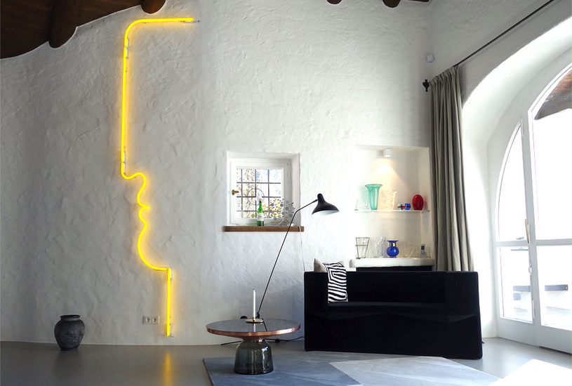 Yellow neon light showing the profile of a face as interior design, installed on a wall, in a modern apartment