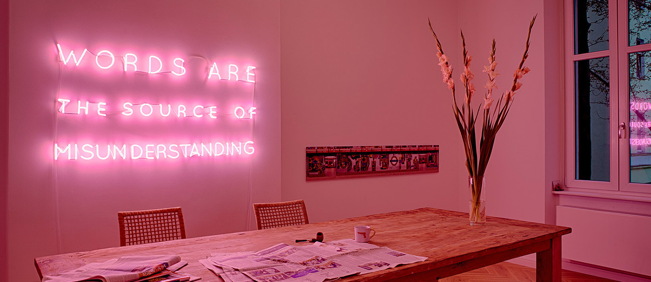 "Neon lettering in pink with the words ""Words are the source of minsunderstanding"" installed on the wall"