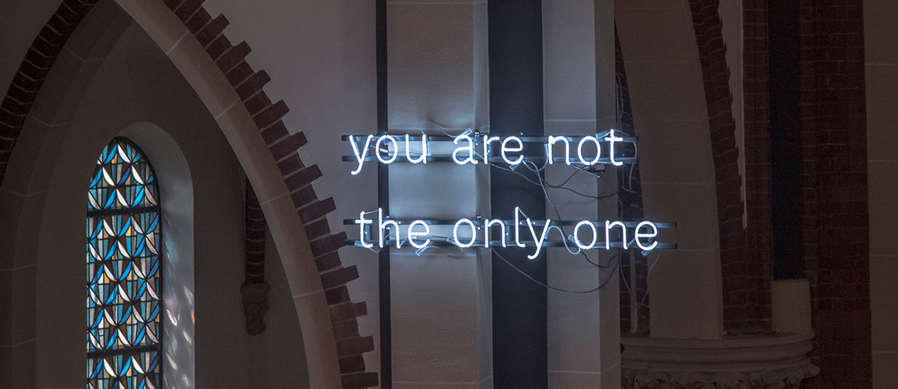 "Neon lettering with the words ""Your are not the only one"" installed in one of the height arches of a church"